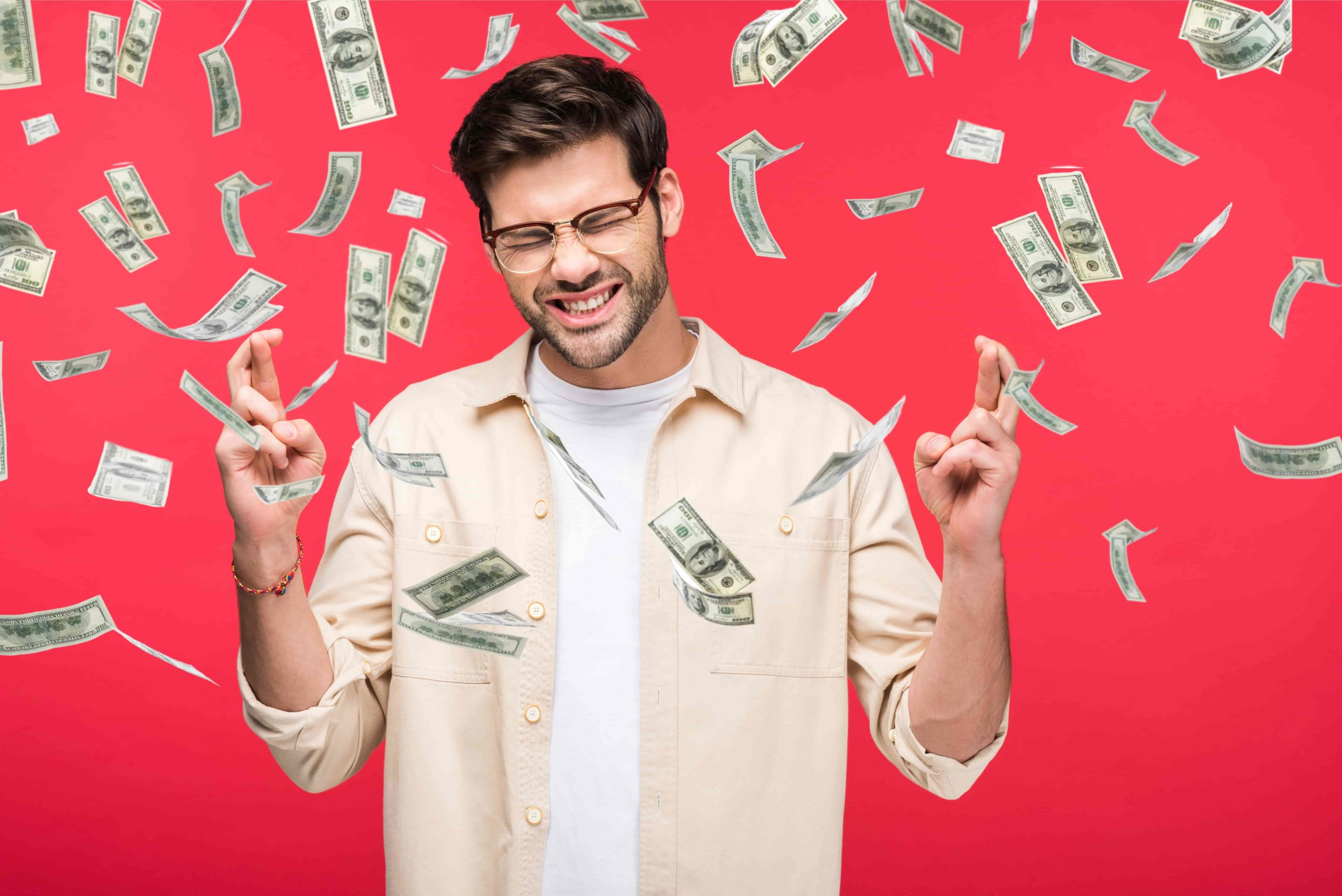 Man crossing fingers with money shower